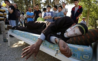 A Palestinian man lying on a bed wears a mask depicting hunger-striking Palestinian journalist Mohammed al-Qiq during a demonstration in solidarity with him in the West Bank village of Bilin, February 19, 2016. (AFP/Abbas Momani)