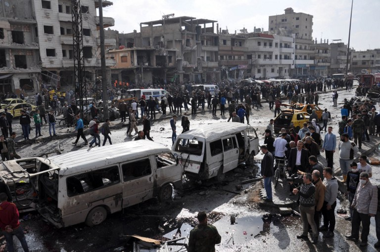 Syrians gather at the site of a double car bomb attack in the Al-Zahraa neighborhood of the central Syrian city of Homs on February 21, 2016. (AFP/STRINGER)