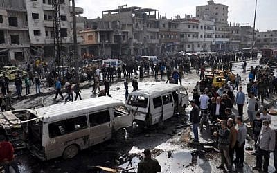 Syrians gather at the site of a double car bomb attack in the Al-Zahraa neighborhood of the central Syrian city of Homs on February 21, 2016. (AFP / STRINGER)