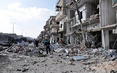 Syrians inspect the damage at the site of a double car bomb attack in the Al-Zahraa neighborhood of the central Syrian city of Homs on February 21, 2016. (AFP/STRINGER)