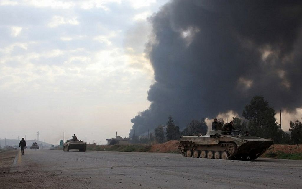 Syrian government forces drive tanks near smoke billowing from Aleppo's thermal power plant after they took control of the area on the eastern outskirts Syria's northern embattled city from Islamic State (IS) group fighters on February 21, 2016. (AFP / GEORGE OURFALIAN)