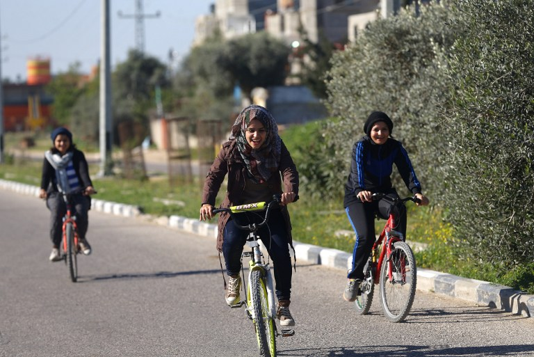 This file photo taken on February 19, 2016 shows (from R-L) Palestinians Assalah Abu Sharkh, Amneh Salman, Nour Sleibi, and Sarah Sleibi, riding their bicycles on a road in Beit Hanoun in the northern Gaza Strip, on February 19, 2016. (AFP / MOHAMMED ABED)