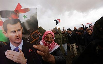 Syrian volunteers and their relatives wave the national flag and portraits of President Bashar Assad as they celebrate at the end of a paramilitary training conducted by the Syrian army on February 22, 2016. (AFP / LOUAI BESHARA)