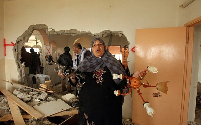 Relatives inspect the damaged interior of the home of Mohammed al-Harub, a Palestinian man accused of opening fire at a junction near Israeli settlements in the West Bank then ramming his car into a group of pedestrians, after it was demolished by Israeli bulldozers near the West Bank village of Dura on February 23, 2016. (AFP / HAZEM BADER)