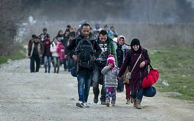 Migrants and refugees from Syria and Iraq cross the Greek-Macedonian border near the town of Gevgelija on February 23, 2016. (Robert Atanasovski/AFP)