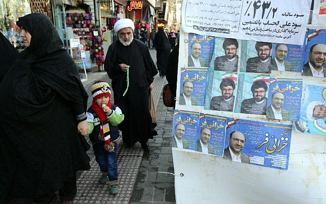 An Iranian cleric walks past electoral posters for upcoming parliamentary elections, near the Hazrat Fatimah Ma'sumeh mausoleum in Qom, on February 24, 2016. (AFP PHOTO / ATTA KENARE)