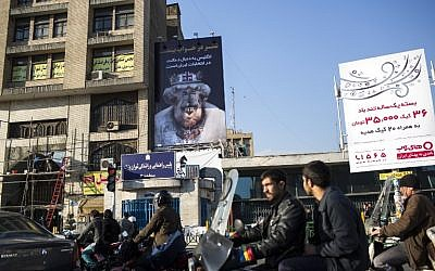 Iranians commute past a banner with a cartoon depicting Britain's Queen Elizabeth II with a camel head and a slogan that reads, 'England wants to interfere in Iran's elections' in downtown Teheran on February 25, 2016. (AFP/Behrouz Mehri)