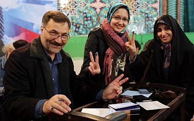 Iranians display their ink-stained finger after casting their ballot for both parliamentary elections and the Assembly of Experts at a polling station in Tehran on February 26, 2016. (AFP / ATTA KENARE)