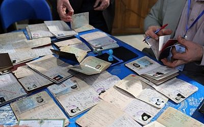 Iranian men register before casting their vote at a polling station in Tehran on February 26, 2016 (AFP / ATTA KENARE)
