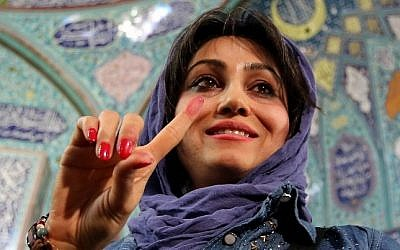 An Iranian woman displays her ink-stained finger after casting her ballot for both parliamentary elections and the Assembly of Experts at a polling station in Tehran on February 26, 2016. (AFP / ATTA KENARE)