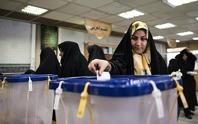 An Iranian woman casts her ballot to vote for both parliamentary elections and Assembly of Experts at a polling station at Massoumeh shrine in the holy city of Qom, 130 kilometers south of Tehran, on February 26, 2016. (Behrouz Mehri/AFP)