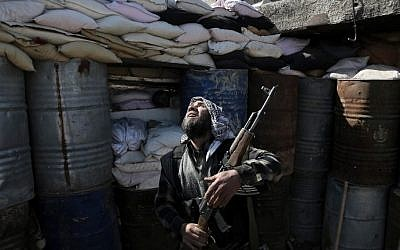 A Syrian rebel fighter from the Islamist Failaq al-Rahman brigade mans a position on the frontline against regime forces in the town of Arbin in the eastern Ghouta region on the outskirts of the capital Damascus on February 26, 2016. (AMER ALMOHIBANY via AFP)