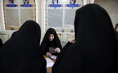 An Iranian election official registers voters for parliamentary and Assembly of Experts elections at a polling station at Massoumeh shrine in the holy city of Qom, on February 26, 2016. (AFP/BEHROUZ MEHRI)