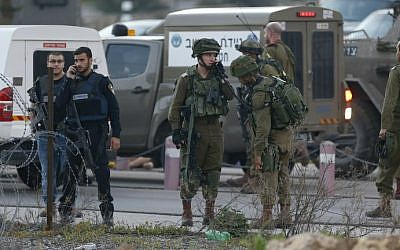 Israeli security forces monitor the area where a Palestinian man tried to stab Israeli soldiers before being shot dead at a checkpoint near Ramallah in the West Bank, February 26, 2016. (AFP/Abbas Momani)