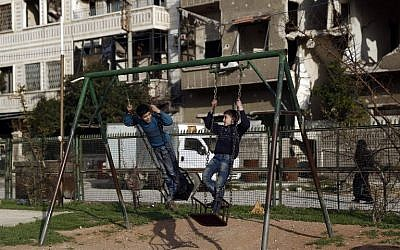 Syrian children play on a swing at a park in the rebel-held town of Douma, on the eastern edges of the capital Damascus on February 27, 2016. (AFP / Sameer Al-Doumy)