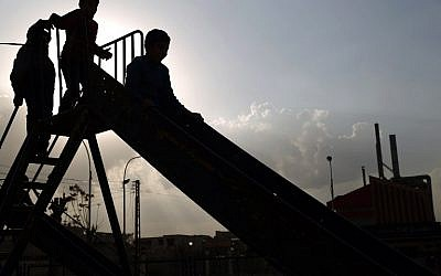 Syrian children play on a slide at a park in the rebel-held town of Douma, on the eastern edges of the capital Damascus on February 27, 2016, on the first day of a landmark ceasefire agreement (AFP / Sameer Al-Doumy)
