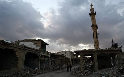 Syrian children walk past heavily damaged buildings in the rebel-held town of Douma, on the eastern edges of the capital Damascus on February 27, 2016, on the first day of the landmark ceasefire agreement (AFP / Sameer Al-Doumy)