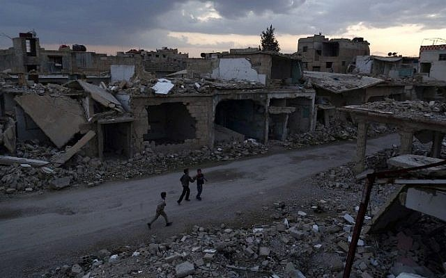 Syrian children walk past heavily damaged buildings in the rebel-held town of Douma, on the eastern edge of the capital Damascus, on the first day of the cease-fire agreement, February 27, 2016. (AFP/Sameer al-Doumy)