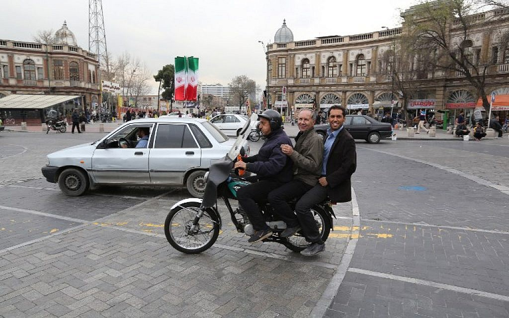 Iranian men take a ride on a motorcycle taxi at Hafez square in central in Tehran on February 29, 2016. (AFP / ATTA KENARE)