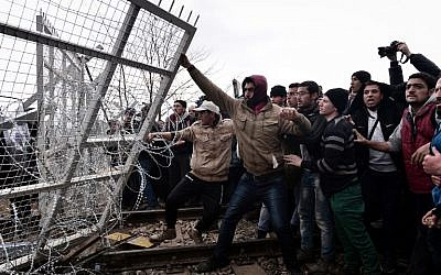 Migrants try to break through a border fence into Macedonia near the Greek village of Idomeni, on  February 29 , 2016, where more than 7,000 people are stranded, as anger mounted over travel restrictions on migrants. (AFP / LOUISA GOULIAMAKI)