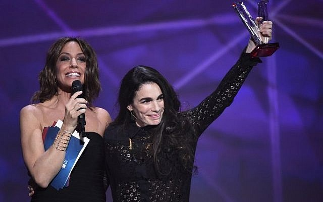 Israeli-French singer-songwriter Yael Naim (R), flanked by French TV host and Master of Ceremony Virginie Guilhaume (L) gestures after receiving the female artist award during the 31st Victoires de la Musique, the annual French music awards ceremony, on February 12, 2016 at the Zenith concert hall in Paris. (Bertrand Guay/AFP)