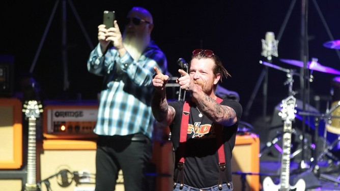 Jesse Hughes (C), the singer of US rock group Eagles of Death Metal, gestures during their concert at the Olympia concert hall in Paris, on February 16, 2016 (AFP PHOTO / JOEL SAGET)