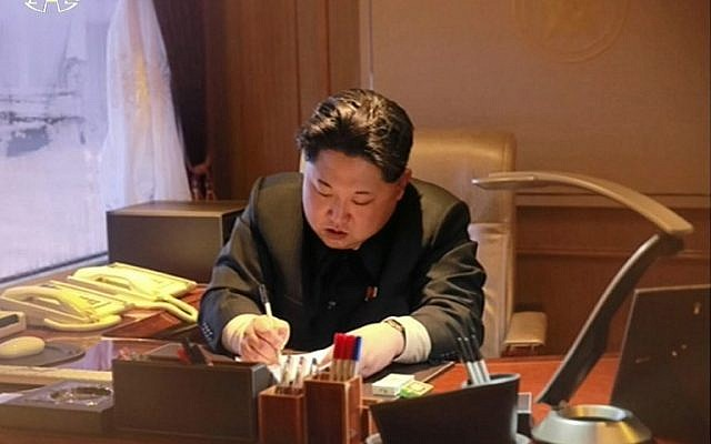Kim Jong-Un signing on a document of earth observation satellite Kwangmyong 4 in Pyongyang, February 7, 2016 (AFP PHOTO / North Korean TV via YONHAP)