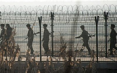 North Korean soldiers patrol next to the border fence near the town of Sinuiju across from the Chinese border town of Dandong on February 10, 2016. (AFP/Johannes Eisele)