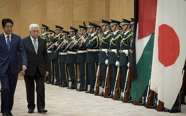 Palestinian Authority President Mahmoud Abbas (2nd L) walks with Japan's Prime Minister Shinzo Abe (L) as they review an honor guard prior to their meeting at Abe's official residence in Tokyo on February 15, 2016. (Nicolas Datiche/AFP)