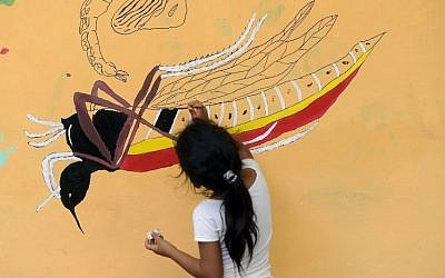 A girl paints a mural that educates people about a mosquito control project in the village of San Diego, in La Libertad, Salvador, on February 4, 2016.(AFP PHOTO/MARVIN RECINOS)