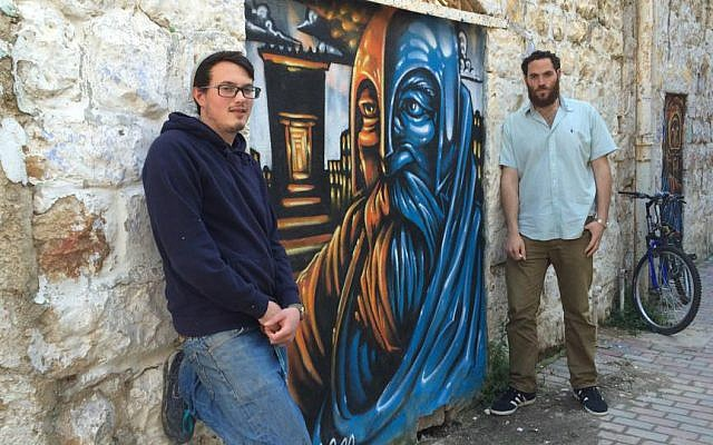 Shuk Gallery artist Solomon Souza (left) and producer Berel Hahn in Jerusalem's Nachlaot neighborhood, standing next to a mural of Judah Maccabee by Souza, February 25, 2016. (Renee Ghert-Zand/TOI)