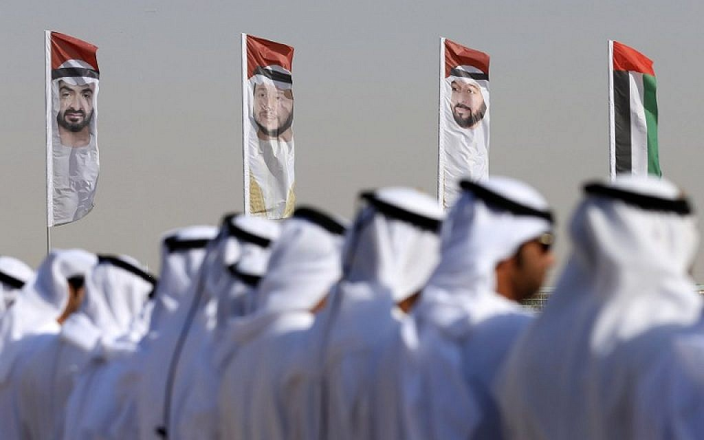 Emirati men perform a traditional dance in front of flags bearing portraits of Abu Dhabi's Crown Prince Sheikh Mohammed bin Zayed al-Nahyan, February 9, 2016. (AFP/Karim Sahib/ File)