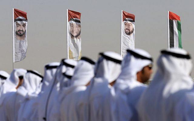 Des hommes émiratis exécutent une danse traditionnelle devant des drapeaux portant le portrait du prince héritier d'Abu Dhabi, le cheikh Mohammed bin Zayed al-Nahyan, le 9 février 2016. (AFP / Karim Sahib / File)
