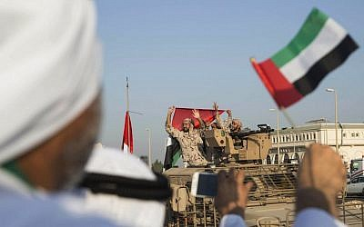 Emirati people wave the national flag as a convoy of UAE military vehicles and personnel travels from Al-Hamra Military Base to Zayed Military City on Nov. 7, 2015. (Ryan Carter-Crown Prince Court - Abu Dhabi/WAM via AP)