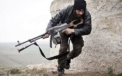 FILE - In this December 17, 2012 file photo, a Free Syrian Army fighter takes cover during fighting with the Syrian Army in Azaz, Syria. (Virginie Nguyen Hoang/AP)