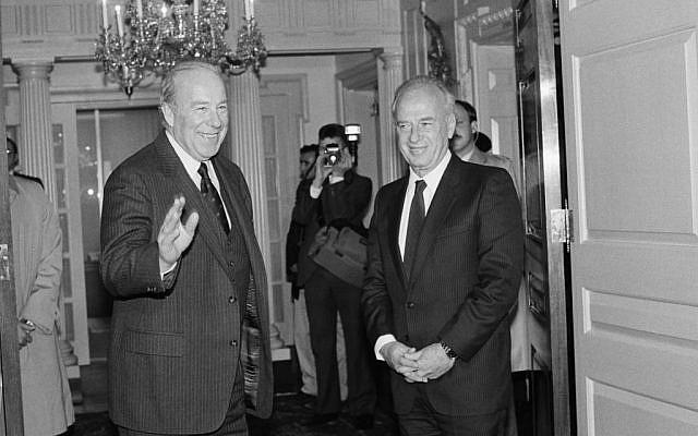 US Secretary of State George Shultz, left, greets Israeli Defense Minister Yitzhak Rabin at the State Department in Washington on January 28, 1985 (AP Photo/Ira Schwarz)