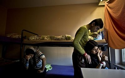 Delphine Qasu, 18, right, a Yazidi refugee from Sinjar, Iraq, is comforted by her brother Dilshad, 17, while crying after talking about their journey to reach Germany, at their new temporary home at Patrick Henry Village, in Heidelberg, Germany, Thursday, December 10, 2015 (AP Photo/Muhammed Muheisen)