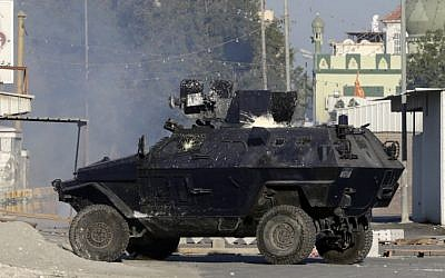 File: A police armored vehicle splattered with paint bombs fires tear gas toward Bahraini anti-government protesters during clashes in Sitra, Bahrain, on Sunday, February 14, 2016. (Hasan Jamali/AP)
