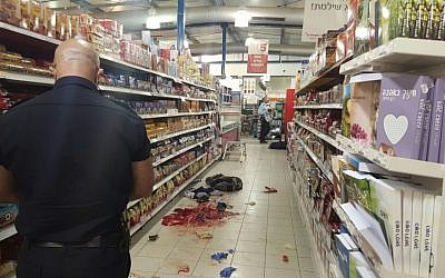 An Israel Police officer documents evidence at the scene of a stabbing attack at the Rami Levy supermarket in the Sha'ar Binyamin industrial park, north of Jerusalem, on February 18, 2016. (Israel Police)