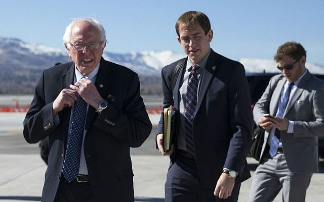 Democratic presidential candidate Sen. Bernie Sanders, I-Vermont, adjusts his tie as he walks to address the media before departing the airport for campaign events in Colorado, Saturday, Feb. 13, 2016, in Reno, Nevada. (AP Photo/Evan Vucci)