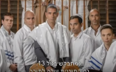 In this screen capture from the new 'Eretz Nehederet' promo, the cast is seen standing around an open Torah scroll. (screen capture: YouTube)