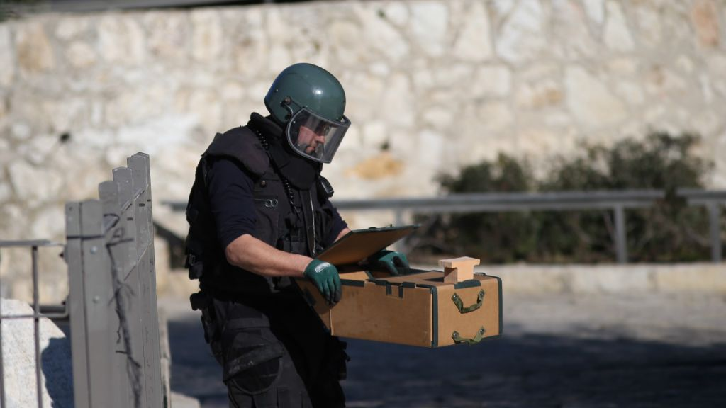 A police sapper removes a suspected explosive device at the scene of a shooting and stabbing attack near Damascus Gate, Jerusalem, February 3, 2016. (Yonatan Sindel/Flash90)