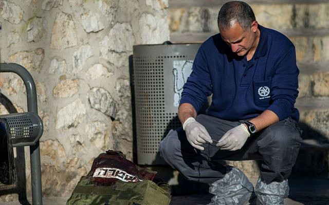 Police investigator near the bodies of Palestinian attackers at the scene of a shooting and stabbing attack near Damascus Gate, Jerusalem, February 3, 2016. (Yonatan Sindel/Flash90)