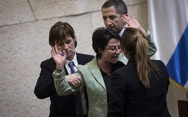 Joint List party member Hanin Zoabi is removed by Knesset security from the plenum session after refusing to leave the podium, February 8, 2016. (Hadas Parush/Flash90)