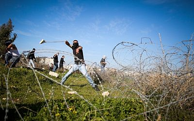 Illustration. Palestinian uses a sling to hurl stones towards Israeli troops  (unseen)  during clashes near the West Bank city of Ramallah on February 12, 2016. (Flash90)