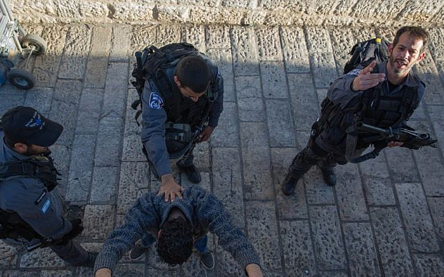Illustrative: Israeli police officers search a Palestinian man at Damascus Gate in Jerusalem on February 15, 2016. (Nati Shohat/Flash90)