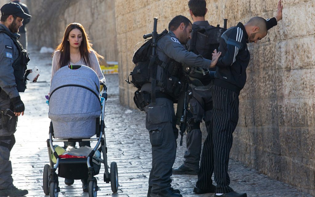 Illustrative: Israeli police officers frisk a Palestinian young man at Damascus Gate in Jerusalem Old City on February 15, 2016. (Nati Shohat/Flash90)