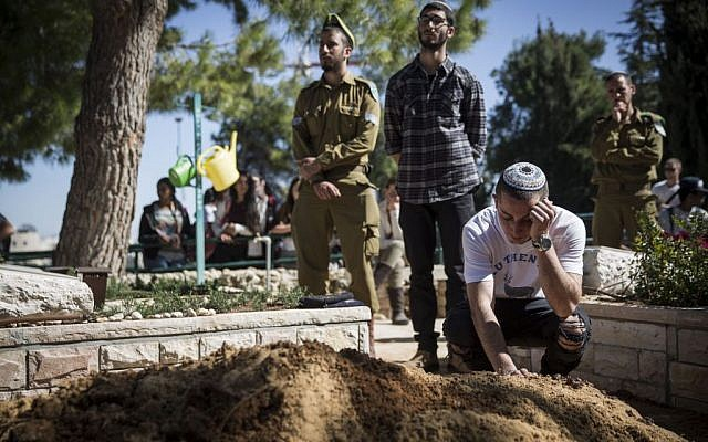Friends seen mourning at the funeral of Tuvia Yanai Weissman,at the Mount Herzl military cemetery in Jerusalem, on February 18, 2016. (Hadas Parush/Flash90)