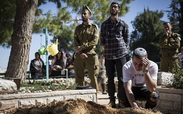 Friends seen mourning after the funeral of Tuvia Yanai Weissman, at the Mount Herzl military cemetery in Jerusalem, on February 18, 2016. (Hadas Parush/Flash90)