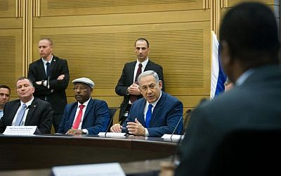 Prime Minister Benjamin Netanyahu attends a conference on Israeli-African relations, organized by Likud parliament member Avraham Negusie (in cap), at the Knesset on February 29, 2016. (Miriam Alster/FLASH90)